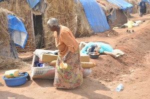 AN OLD WOMAN GATHERING HER BELONGINGS TO LEAVE