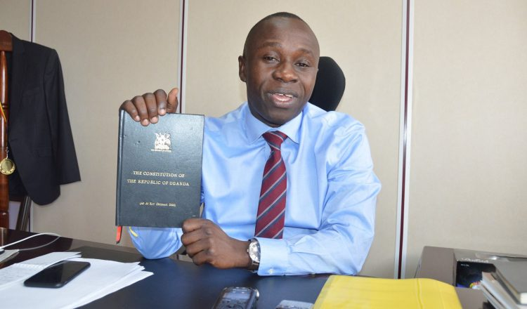 Peter-Ogwang-displays-a-copy-of-the-Constitution-at-his-office-750x440